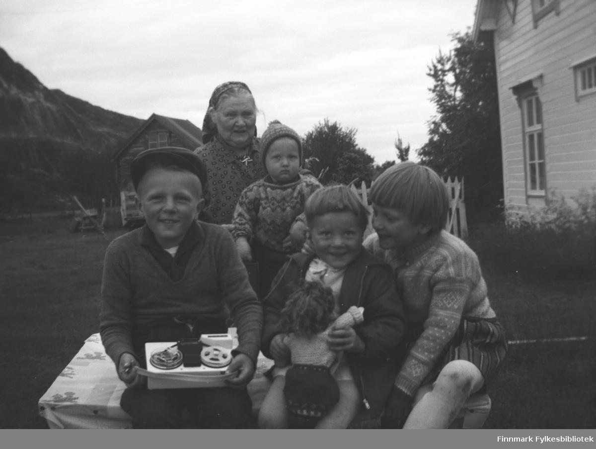 Kathinka Mikkola med fire barnebarn på Mikkelsnes, ca. 1968. Fra venstre: Asle Lindseth, Kathinka Mikkola med Karl Vidar Lindseth på fanget, Inger og Anita Lindseth. Asle holder en liten båndopptaker og Inger har ei dokke