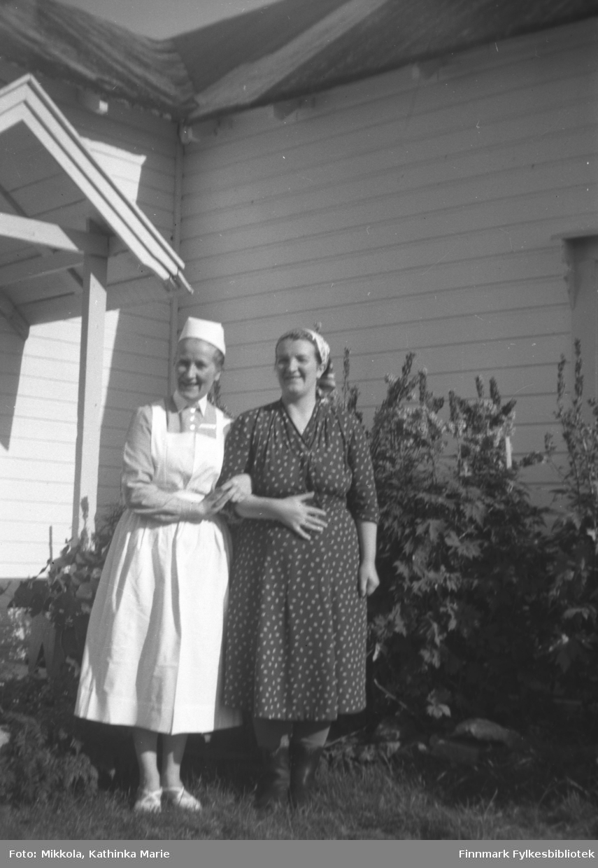 Herlaug Digre i sykepleieruniform ved inngangen til Mikkelsnes, arm i arm med søsteren Astrid Lindseth. Bildet er tatt ved samme anledning som 05007-235 og 05007-300