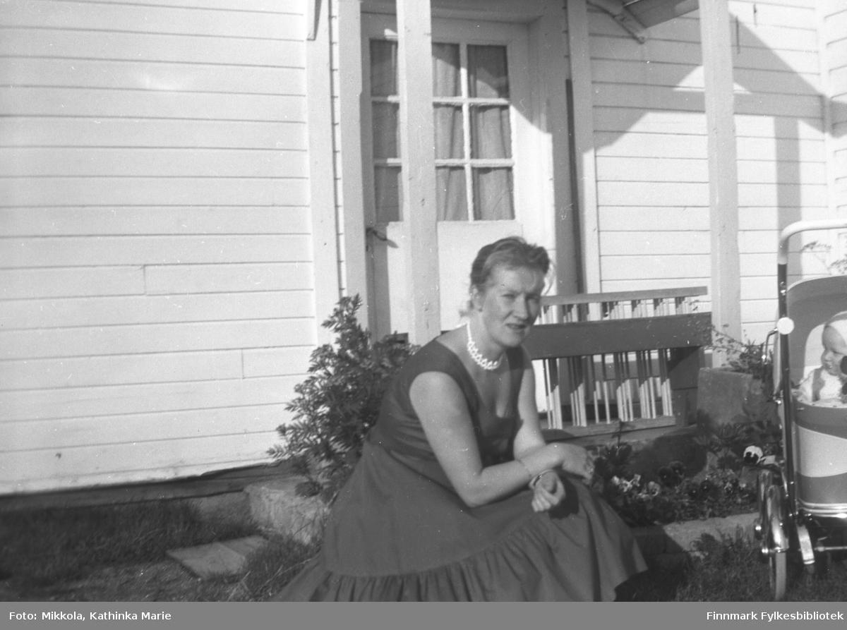 Herlaug Digre med et ukjent barn i vogn utenfor Mikkelsnes. Hun har sommerkjole, og frodige hageblomster står frodige i den lune solkroken ved inngangsdøra