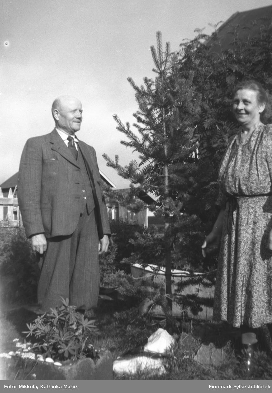 Mangor Nilsen på besøk på Mikkelsnes sammen med kona. Her står de i hagen ved et ungt furutre. Bildet er tatt ved samme anledning som 05007-272 og 05007-301