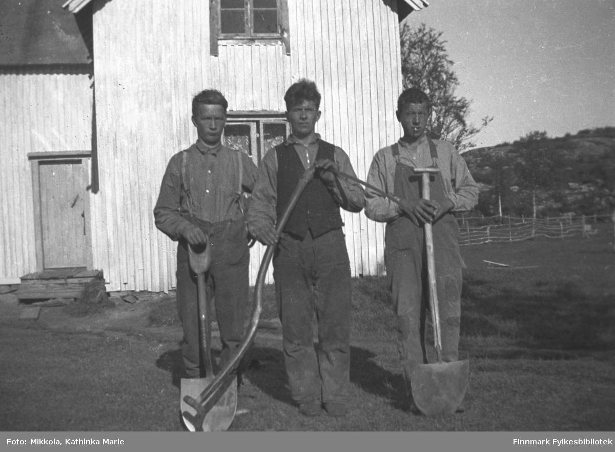 Tre unge menn med spader og ljå, fotografert foran et lyst hus. Vi vet ikke hvor bildet er tatt, men det er antakelig i Sør-Varanger