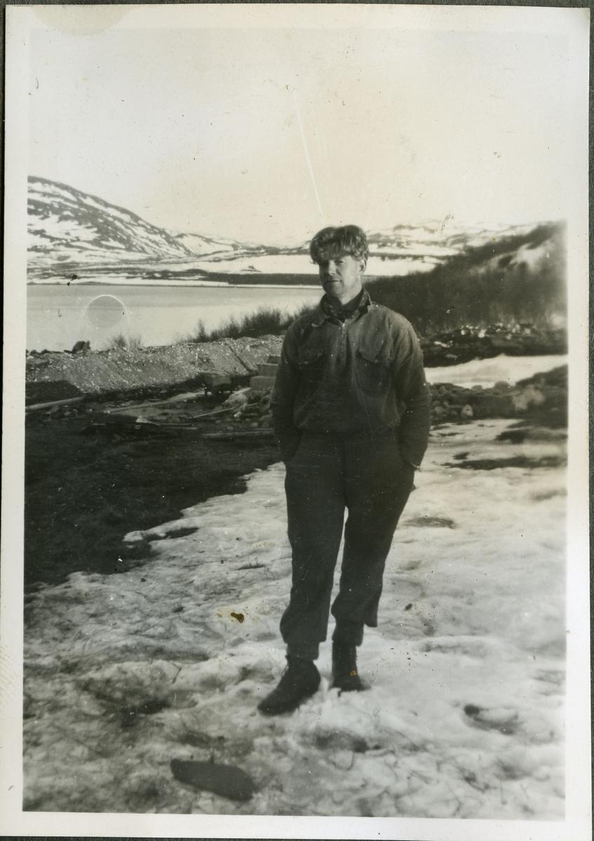 Fotografi av en ukjent mann på skiferbruddet i Friarfjord. Mannen er trolig en arbeider på stedet. Han er kledd i skjorte, bukse, sko og et skjerf rundt halsen. Bak ham kan man se steiner og byggeredskaper. I bakgrunnen ser man havet og fjell. På bakken ligger det snø.