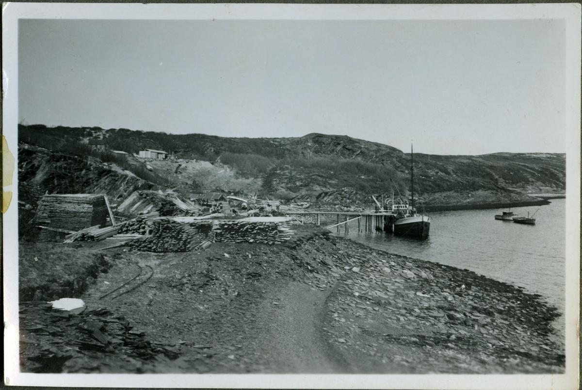 Skiferbruddet i Friarfjord opererte med egen båt til transport. Her ser man kaia og fjæra avbildet. Lengre opp i bakken kan man se fjøset (øverst i venstre hjørne). Til venstre kan man se store hauger med tremateriale som er stablet opp.