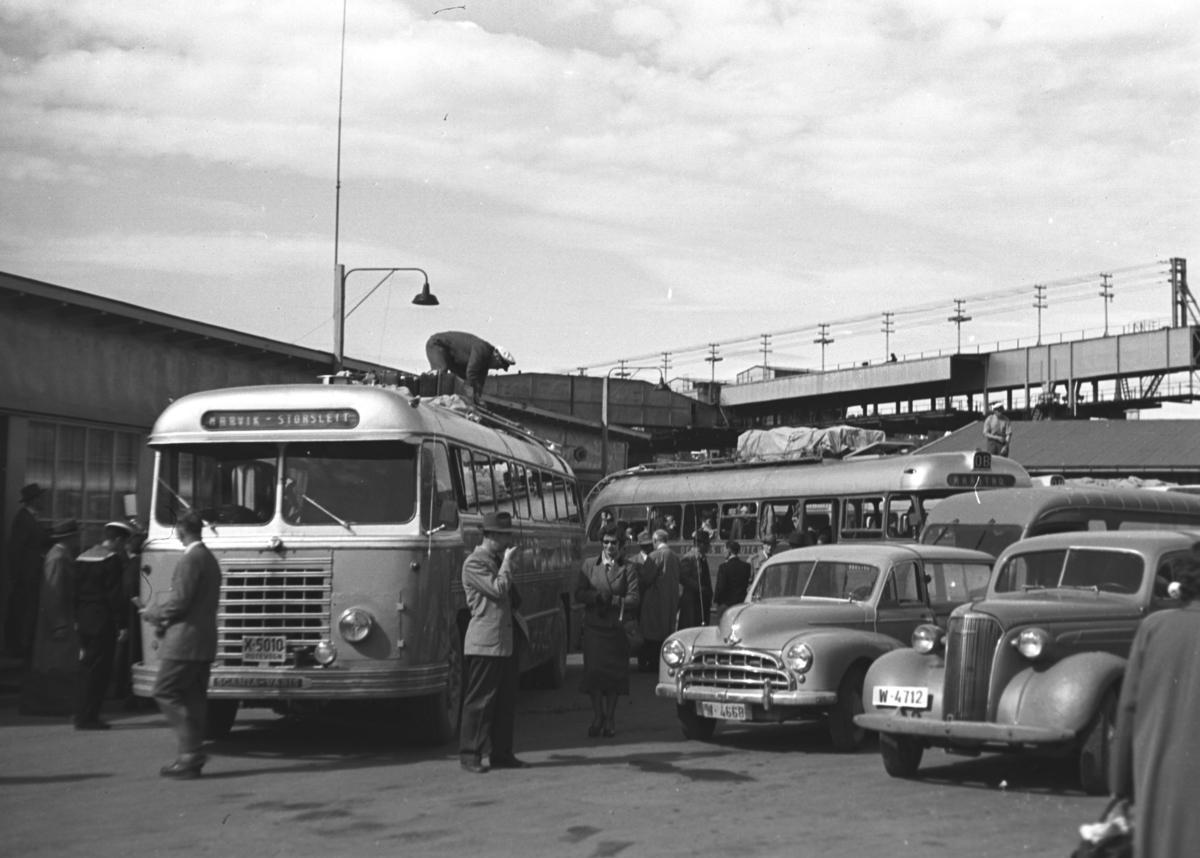 """Stedet er Narvik. Bilene har fylkesbokstav W for Nordland, første navn i skiltkassen til bussen t.v. er trolig Narvik og konstruksjonen i bakgrunnen over bilene er kanskje noe av losseanlegget til LKAB? Kjøretøyene er fra venstre en Scania-Vabis buss (kfr. navneplata på støtfangeren) og trolig """"Narvik-Storslett"""" i skiltkassen. Registreringsnummeret er kanskje X-5010 og den kan evt. tilhøre Troms Innland rutebil. Det foregår trolig pålessing på bagasjegrind på taket. Deretter en Morris Oxford ca. 1950-53 stasjonsvogn og 1937 Chevrolet . Over  de to sistnevnte skimtes trolig en Renault kassebil. Bussen i bakgrunnen har """"Harstad"""" i skiltkassen. Høybanen DEMAG ses i bakgrunnen."""