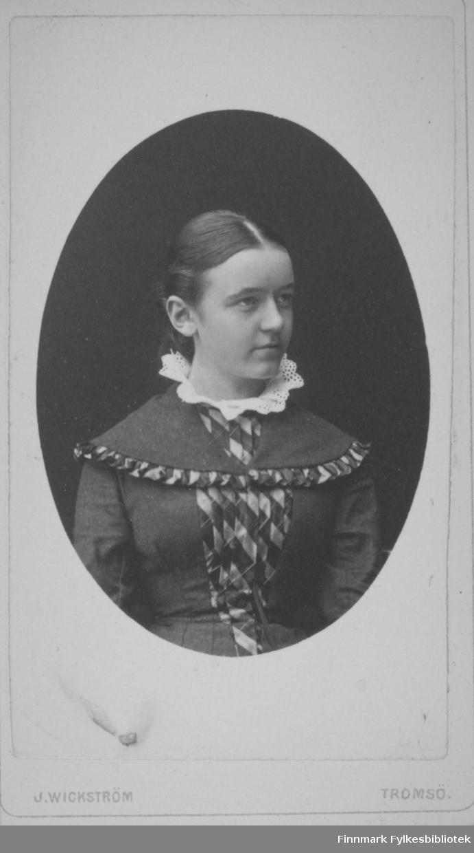 Portrett av en dame i mørk overdel med en hvit, heklet krage. Et pyntebånd går på tvers over brystet. Portrettet er tatt hos Wickstrøm i Tromsø.