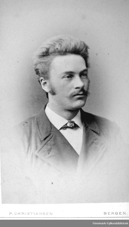 Portrett av en mann. Han har en mørk dressjakke og hvit skjorte. Portrettet er tatt hos P. Christiansen Photographiske forretning i Bergen.