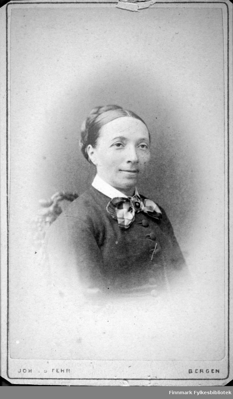 Portrett av en dame i mørk overdel. En hvit skjortekrage og et tørkle ses i halsen. En liten del av en stolrygg med uskjæringer ses rett bak henne. Portrettet er tatt hos fotograf Joh. v. d. Fehr i Bergen.