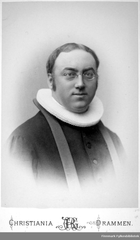 Portrett av en mann i presteklær. Han har en hvit prestekrage rundt halsen, en mørk prestekjole og lorgnetter på nesen. Portrettet er tatt hos Rude.