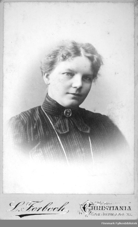 Portrett av en dame i en mørk, stipete bluse. En brosje ses i halsen og et kjede henger rundt halsen.