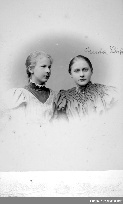 Portrett av to unge damer, Gerda Buck til høyre på bildet. Damen til venstre har en lys overdel med et mørkere parti i halsen og en smal blondekrage. Gerda har en mørkere overdel med tøymønster og høy krage.