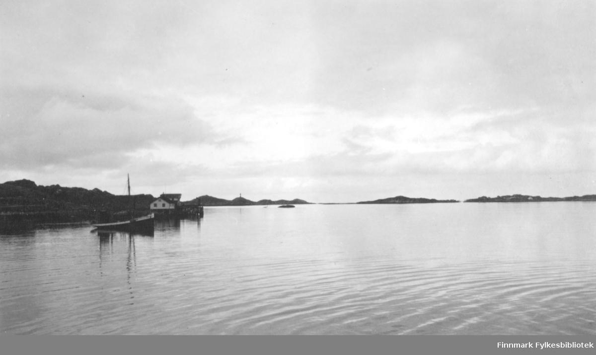 En sommerdag på Ingøy. Blikkstille hav og skyet. En båt ligger fortøyd på havna og et hvitt hus ligger i sjøkanten. Et sjømerke står på en liten topp og en holme ses litt til høyre for sjømerket. Flere små øyer ses mot horisonten til høyre på bildet.