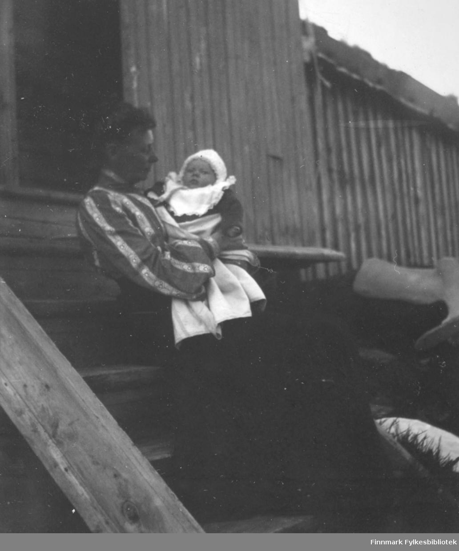 En dame sitter på trappa og holder et spedbarn i armene. Dama har en stripet overdel og mørkt skjørt. Spedbarnet har en mørk overdel, lys lue og en smekk i halsen. Barnet er pakket inn i et lyst teppe. Trappa de sitter på er av tykke treplanker med fire  trinn og døra bak dem står åpen. Huset har stående panel og det er noen gresstuster rundt trappa. Det har et lite tilbygg til høyre på bildet