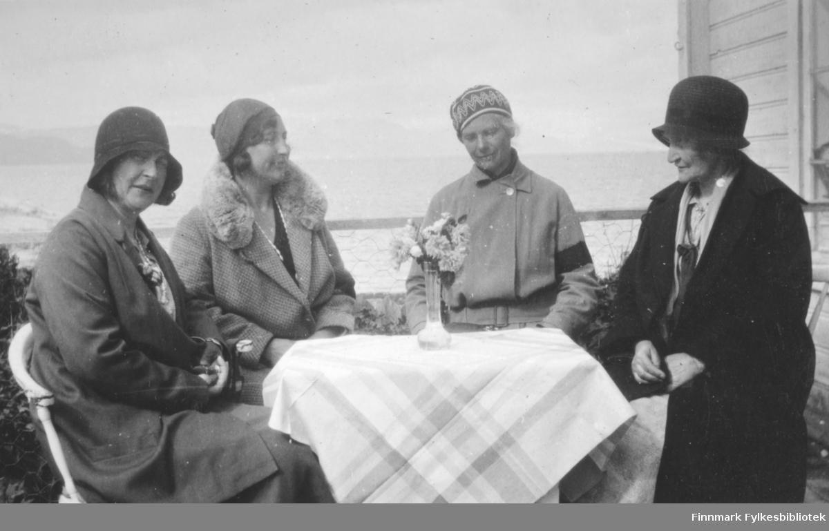 Fire damer på verandaen en ganske overskyet sommerdag. De sitter på hvite pinnestoler rundt et bord med en stripete duk og en blomstervase på. De to nærmeste har mørke hatter, de to andre luer. Alle har kåper på seg og nr. to fra venstre har kåpe med skinnkrave. Litt av husveggen med sprossevindu ses til høyre i bildet. Bak damene ses litt av Altafjorden og deler av et rekkverk med en tverrgående planke og netting.