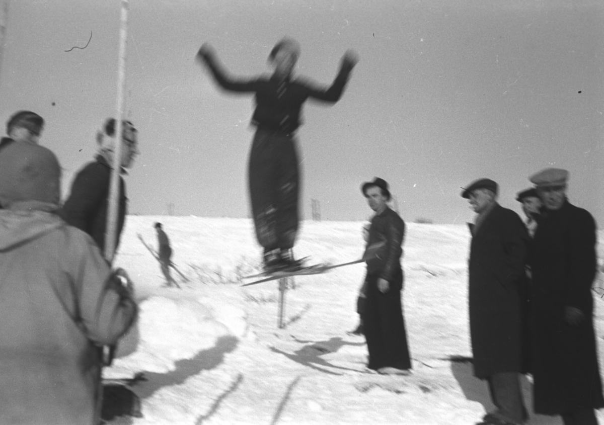 Flere personer står og ser på svevet til en skihopper. Personer og sted er ukjent.