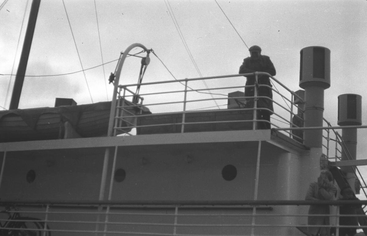 To ukjente personer fotografert på dekket av en stor båt. Stedet der båten ligger er ukjent.