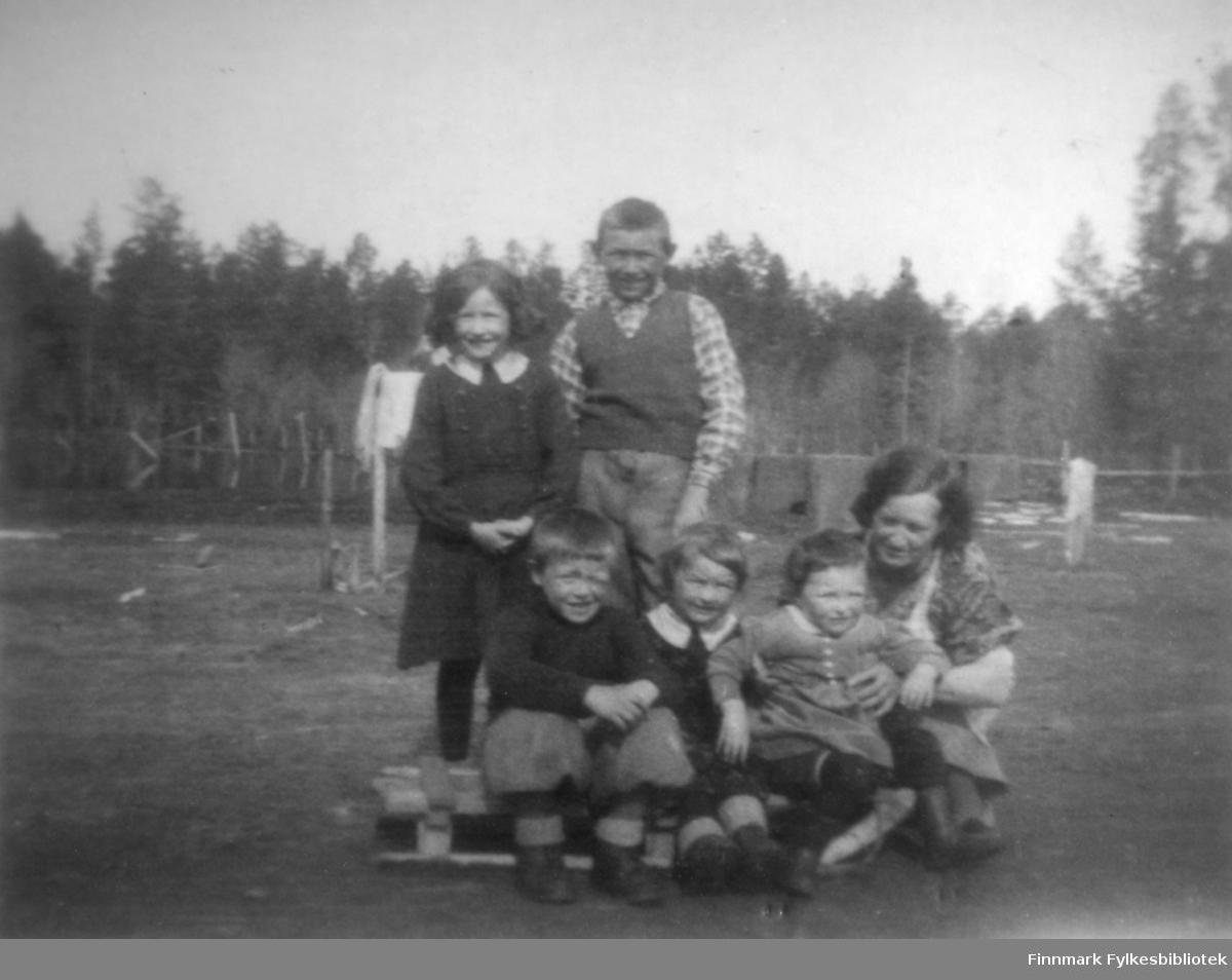 Fotografi av Jenny Jakobsen og barna. Bildet er tatt hjemme i Øvre Alta. Bakerst står Aud og Aksel. Foran fra venstre sitter: Terje, Magnhild og Kari på en kjelke. Jenny sitter på huk til høyre. Klesvask henger til tørk. I bakgrunnen ser man også skog