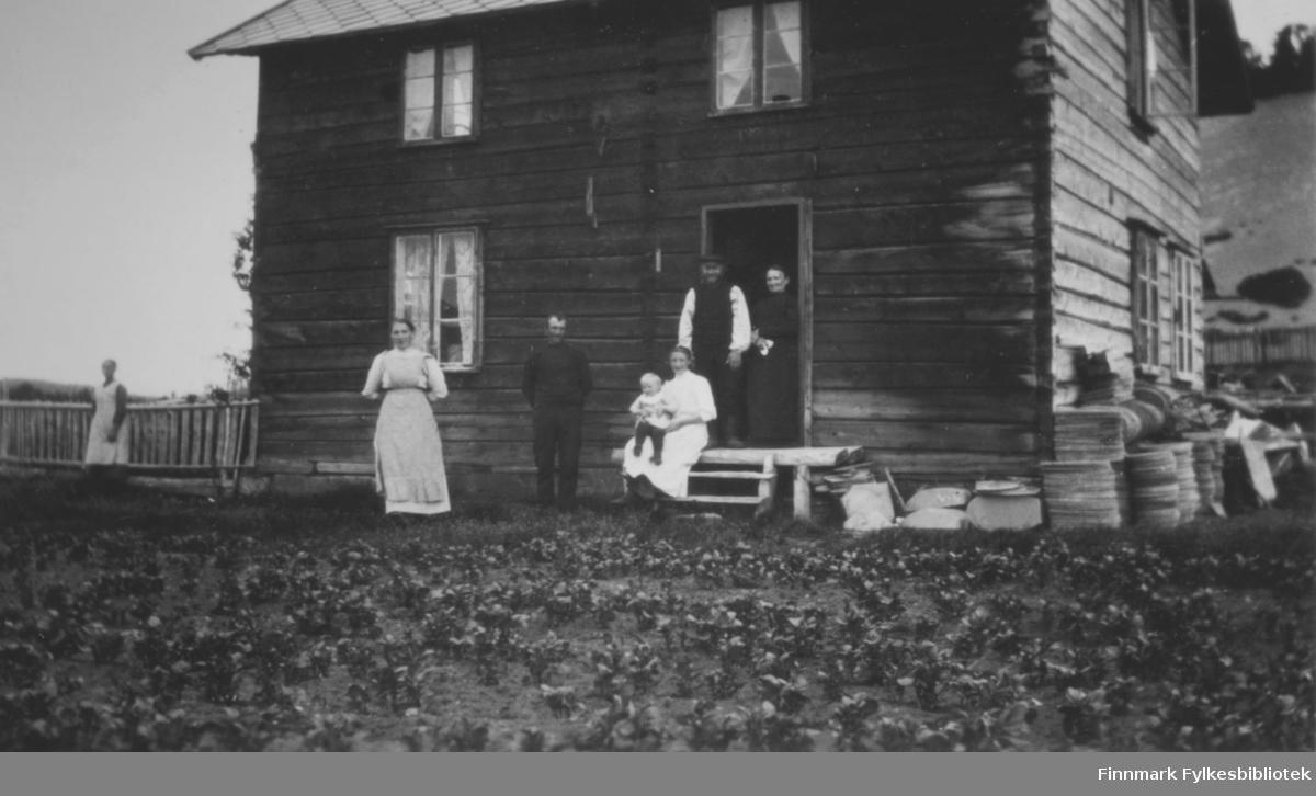 Utenfor et trehus på Elvebakken. I døråpningen står det en mann og en kvinne. På trappen sitter Hilja Olsen med Theodor på fanget. Det står en kvinne og en mann foran huset. Det står også en kvinne ved gjerdet, til venstre i bildet. I tekst til bildet står det at Ole og Grete Arnesen er to av personene på bildet. Det ser ut som steinheller som ligger oppmot husveggen