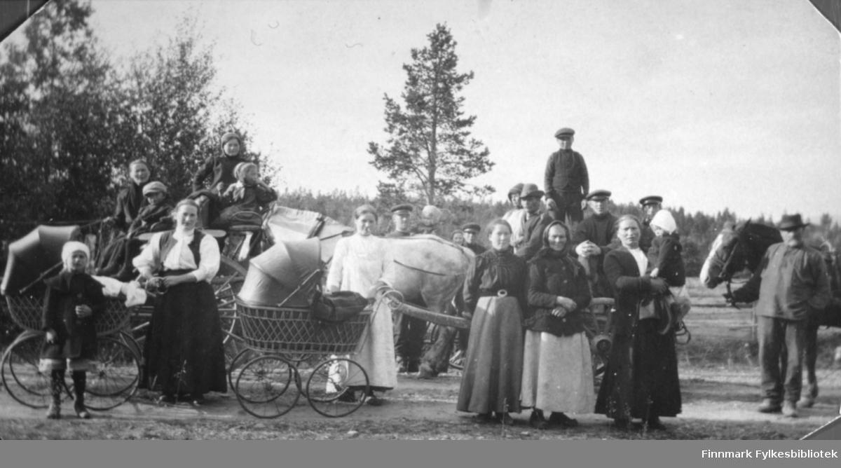 Mange mennesker som står på en grusvei. Det er både kvinner, menn, og barn. På bildet er det hester med vogner, hvor det sitter folk oppi. Det er også to barnevogner med kalesjer på bildet. I bakgrunnen er det trær
