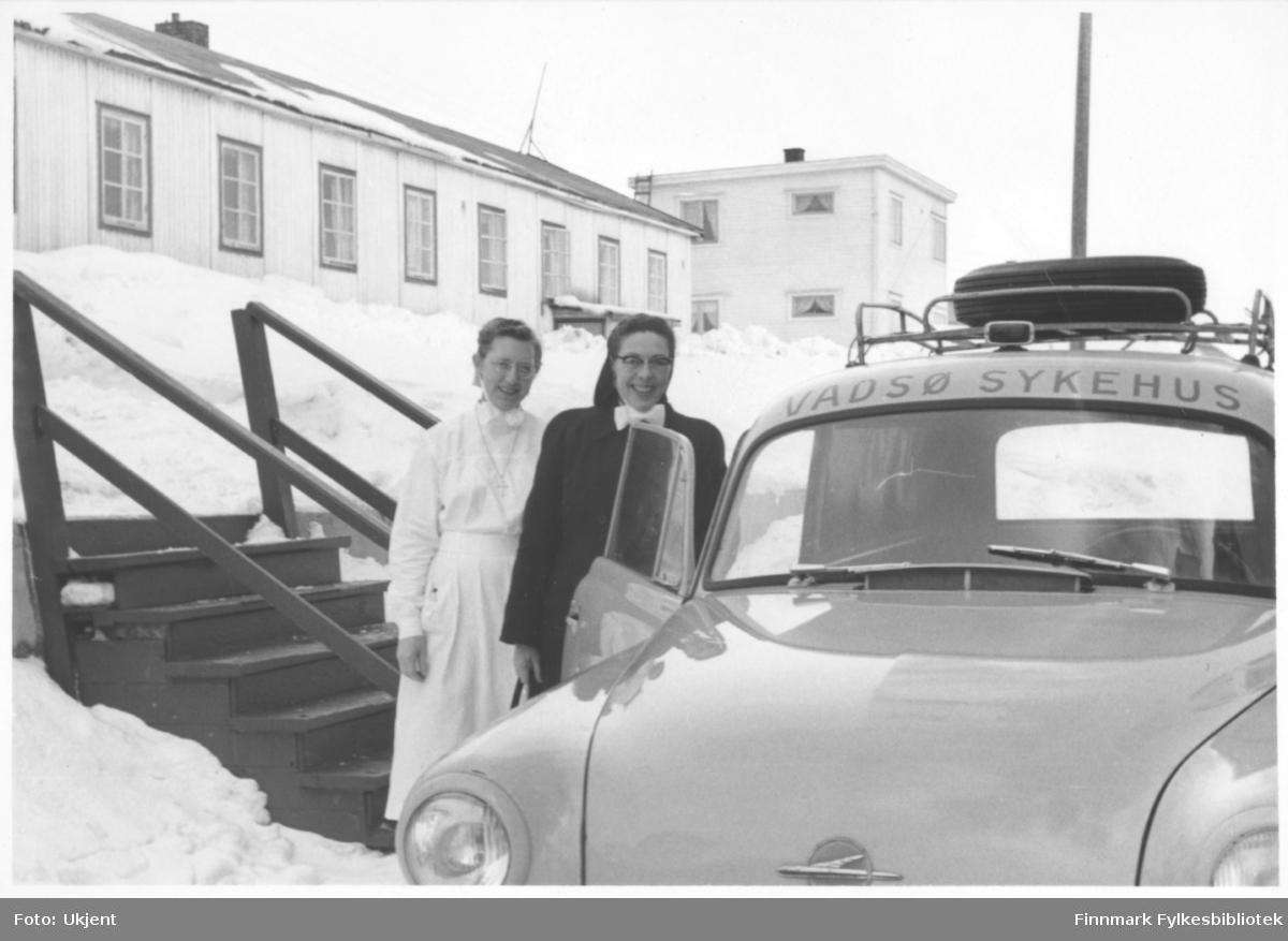 Reisende sykepleier Ingeborg Søvik står ved siden av en bil (Opel Olympia varebil årsmodell 1953-57). Til venstre for henne står oversykepleier Gudrun Byholt. I bakgrunnen kan man se søsterbrakka. Gudrun har på seg uniform og et kors rundt halsen. Ingeborg har på seg jakke. De har begge briller. På taket på bilden kan man se bagasje. Ved siden av kvinnene kan man se en trapp. Det er snø på bakken. På bygningene kan man se vindu og skorsteiner.