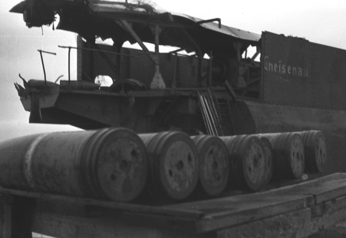 """Bildet fra ett av hovedskytsene i Kiberg fort - tatt etter frigjøringen. En vogn med granater ligger ved siden av en stor kanon med navnet """"Gneisenau"""" malt på siden. Kanonene hadde kaliber 28 cm og en rekkevidde på 35 kilometer. Kanonene fikk navn etter tyske slagskip og kystfortet i Kiberg var det største i Finnmark."""
