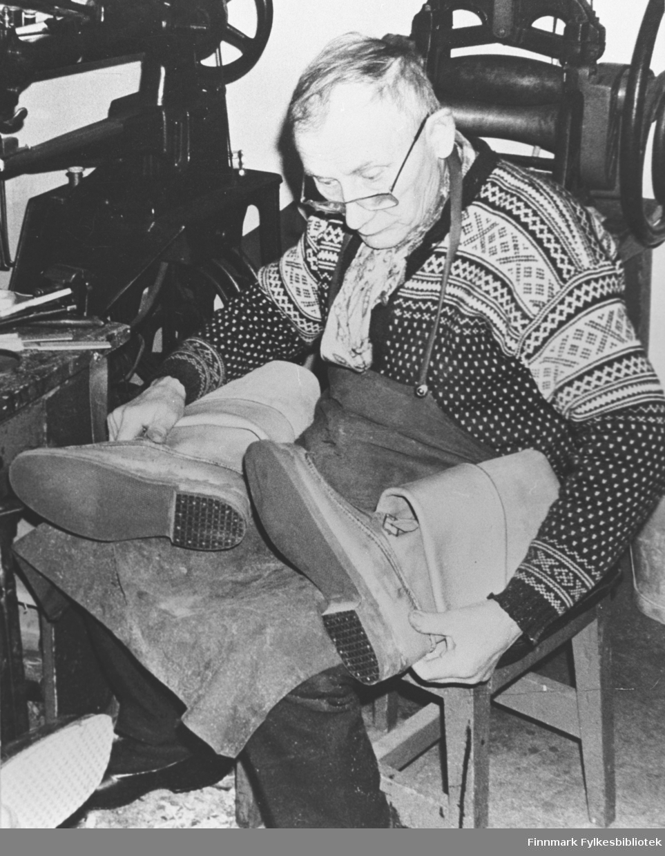 Skomaker Bernhard Eriksen i arbeid. Han sitter på stolen og ser ned på selvsydde biekso han har på fanget sitt. På bakgrunn står en symaskin og en annen maskin (presse?).