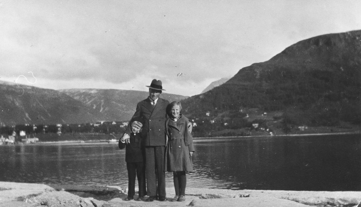 Bildet er tatt i Tromsø. Fra venstre Rakel Lein, lærer Ødejord og Lars Ødejord. I bakgrunnen ser vi sjø og fjell. Mannen er i mørk dress og hatt. Den ene amen holder han rundt jenta som har kåpe med belte på. De andre armen holder han rundt en gutten som har mørke klær på.