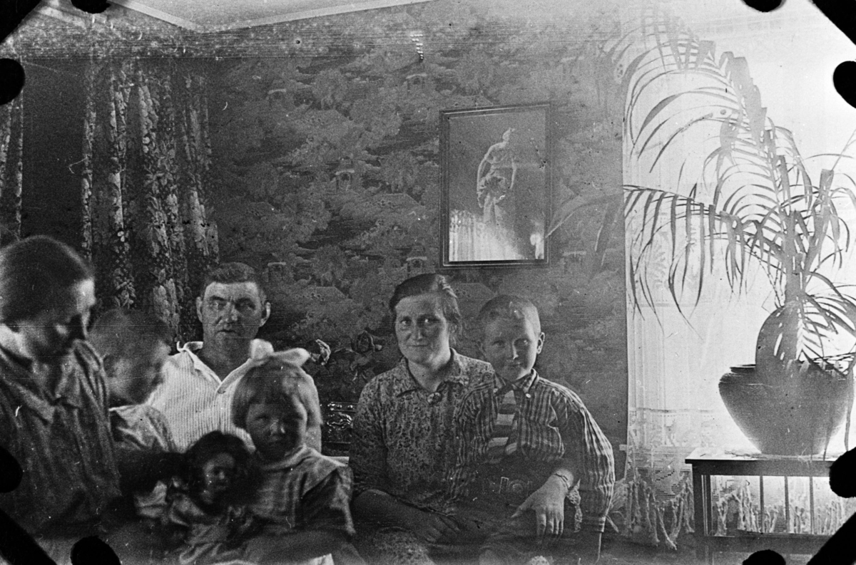 Gruppebilde tatt i stua hos Golla Fuglevik i Syltefjord. Fra venstre Kathinka Lein,ukjent, Enok Lein, Alma Holmen med Reid Holmen på fanget. Foran Rakel Lein med dokke på fanget. Til høyre en stor grønnplante på et bord foran vinduet. Mønstret tapet på veggene. På veggen henger et bilde. Til venstre portierer foran en gøråpning.