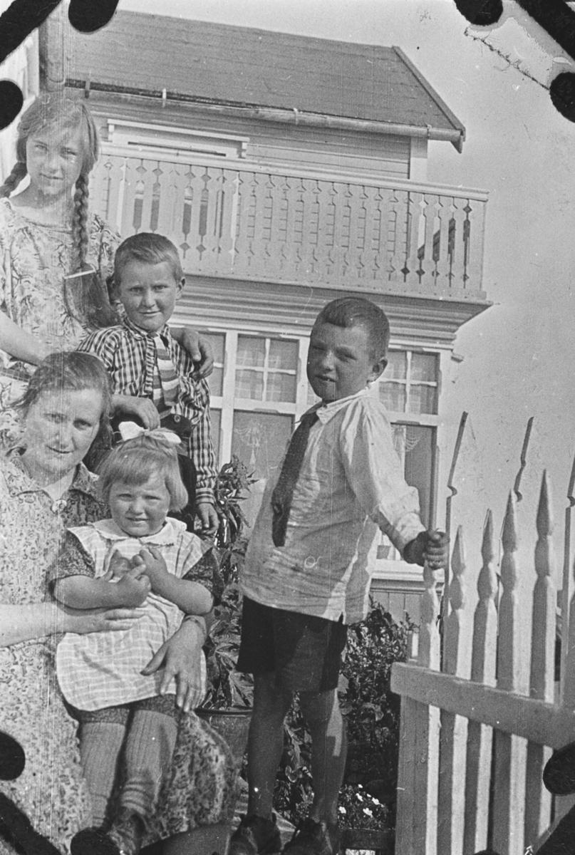 Gruppebilde tatt utenfor huset til Golla Fuglevik i Syltefjord. Bakerst fra venstre: Lilly Lein med fletter og blomstret kjole, Reid Holmen i rutet skjorte og stripet slips, Tore Lein med korte bukser, hvit skjorte og mørkt slips. Alma Holmen i blomstret kjole med Rakel Lein På fanget. Rakel har rutet kjoleforkle utenpå kjolen, og hvit sløyfe i håret.  Tore holder i gjerdet, bak ser vi litt av blomster.  Huset har veranda i 2 etage. Under veranden er det store vinduer.