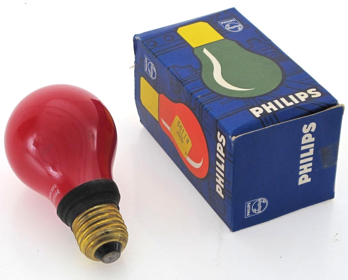 Mørkeromslyspære i eske. Lyspæren er rød, og esken inneholder flerspråklig tabell for bruk. Prislapp. Esken ene flipp er avreet og mangler.