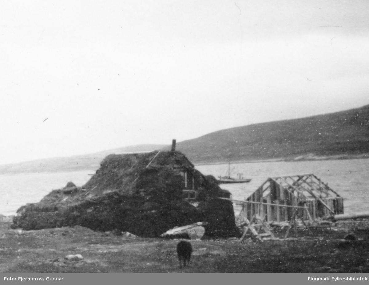 Et lite hus dekket av torv, sansynligvis for isolering. Et lite bygg som kan være et naust/sjøbod, er under oppføring like ved. En sjark ligger fortøyd ute på sjøen. Stedet er ukjent. Bildet er tatt våren 1946.