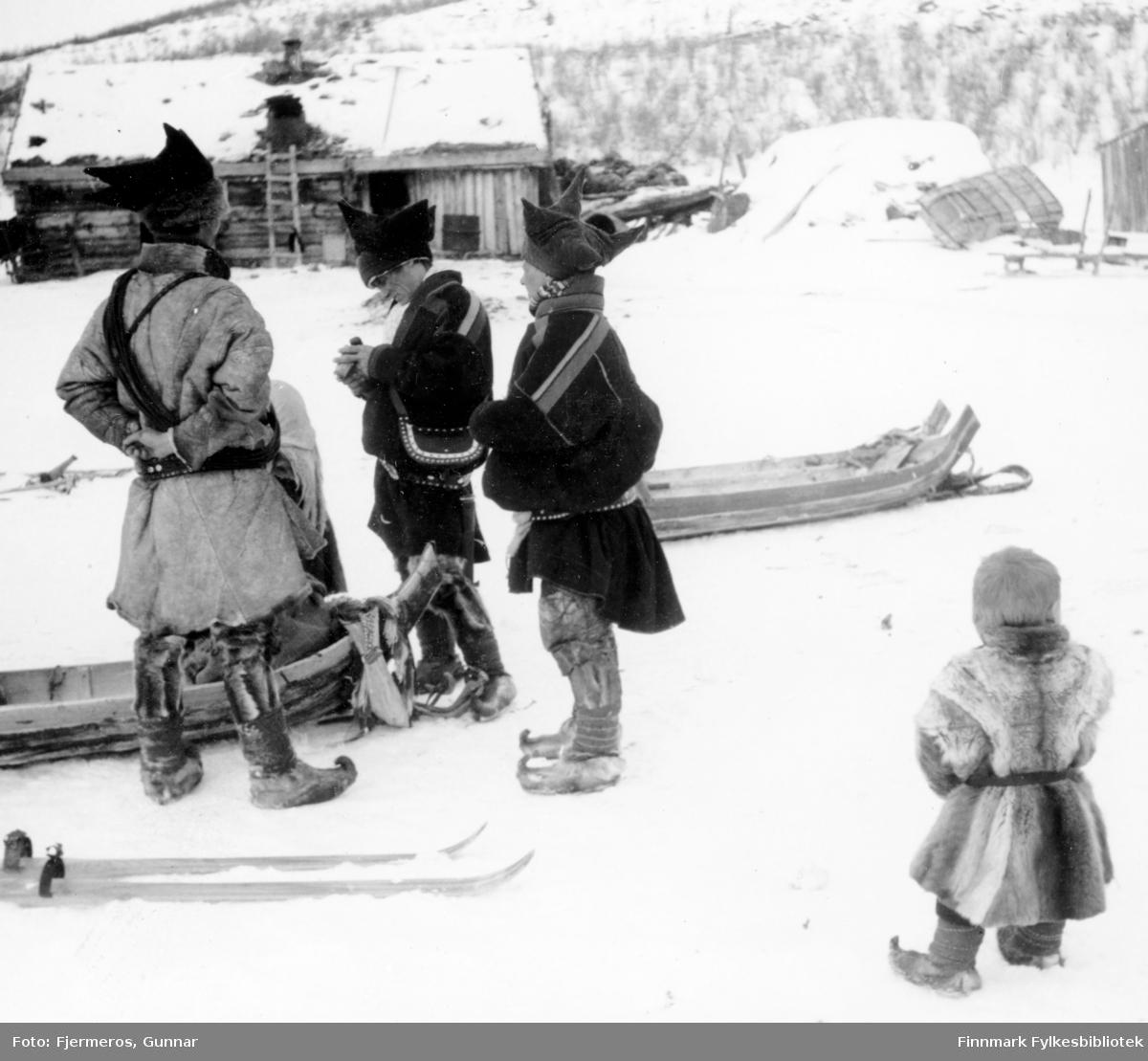 Fotografi av tre voksne og et barn i sameklær med noen sleder og ski på den snødekte bakken. Bildet er tatt på Jergul i påsken 1947.