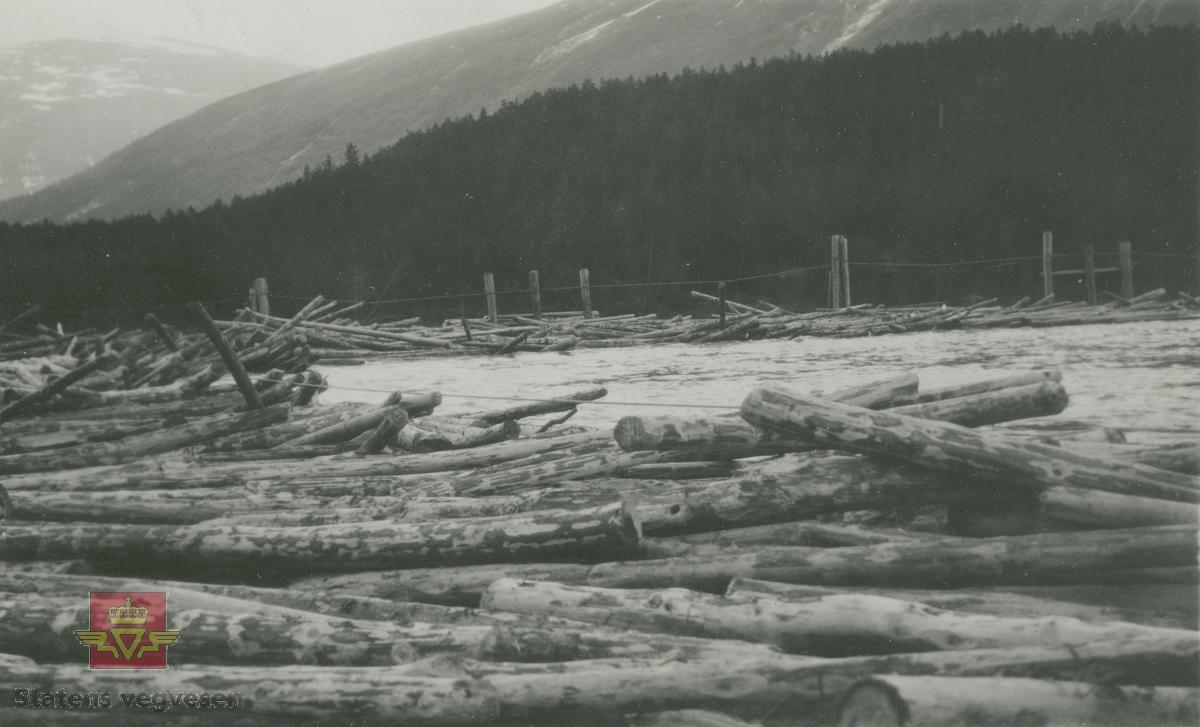"""Album fra 1929-1943. Tømmerfløting.  Informant 16.10.2020: """"Det kan være på Harsheimhølen, ser markule og Lendfjellet i bakgrunn. Harsheimhølen ligg ca. 1 km vest for Bismo i Skjåk, der var det lenser og inntak av tømmer til gamle Skjåk almenning's sagbruk mens fløytinga pågjekk. Røysene til lensa ligg fortsatt synlege i elva, om du kjøret R15 på motsatt side av elva i forhold til der bilde er tatt.  Lendfjellet ligg i Skjåk, der også den kjende lendbreen med forhistoriske funn ligg. Markule ligg på tverrfjellet, bak tverrfjellet ligg Lundadalen."""""""
