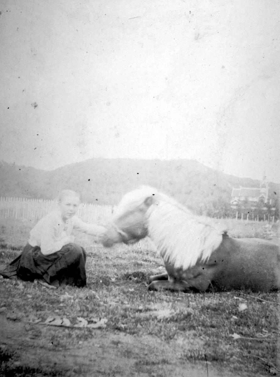 """Andrea Håheim og hesten """"Ola"""". Andrea klapper hesten som ligger på bakken. Til høyre i bakgrunnen kan man se en kirke."""