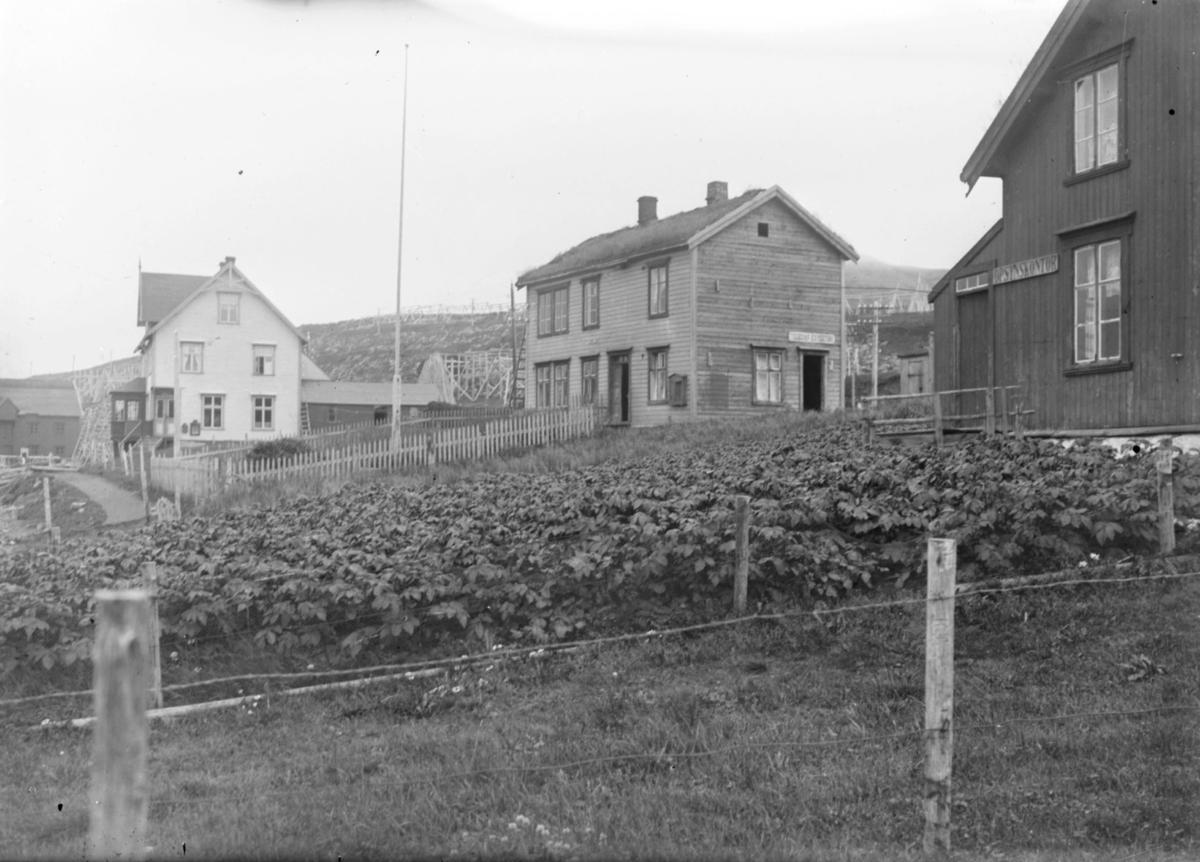 Nergaardgården og Isaksengården og en tredje gård fotografert på sommertid. I forgrunnen ser man en potetåker.  Opsynskontoret står det på veggen på det første huset.  Isaksengården hadde telegrafstasjon  (skilt på veggen).  Bakerst i bildet ser man  Nergaardgården. Alle husene er toetasjeshuser med hager, uthuser og fjøs. Huset til høyre tilhørte også Isak Isaksen, hans sønn Gustav overtok alt etter hans død. Huset til høyre overtok senere Gustavs datter Gunvor og hennes mann Leif Johansen. Dette huset inneholdt også oppsynsstasjon for fiskeriene.