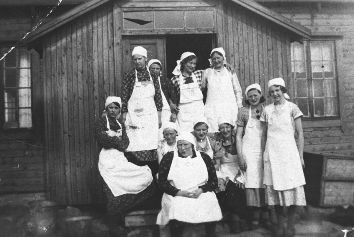 Jentene på husstellkurs fotografert på trappa ved et hus. Alle åtte unge kvinner og tre kvinner i 30-40 årene er kledd i hvite forklær og hvite tørkler.