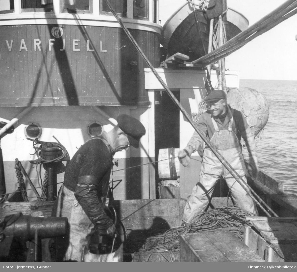 """To menn i arbeidsklær på dekket til båten """"Varfjell"""" som er på Håkjerringfiske. Personene og stedet båten fisker på er ukjent."""