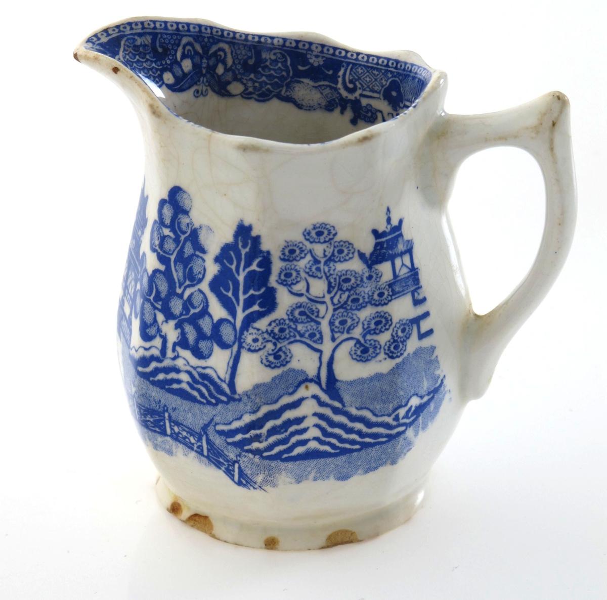 Deler av  kaffeservise, mønster   Willow Pattern,  1880 årene,  Egersund Fayencefabrik. Stemplet. (type 1880-88).    Stentøy,  hvitt med blå påtrykt dekor, dels gullkant,   AAM.1205l-53. Asjetter, 3 stk.   AAM.12054-58 3 kopper med 5 skåler.  AAM.12059. Fløtemugge.