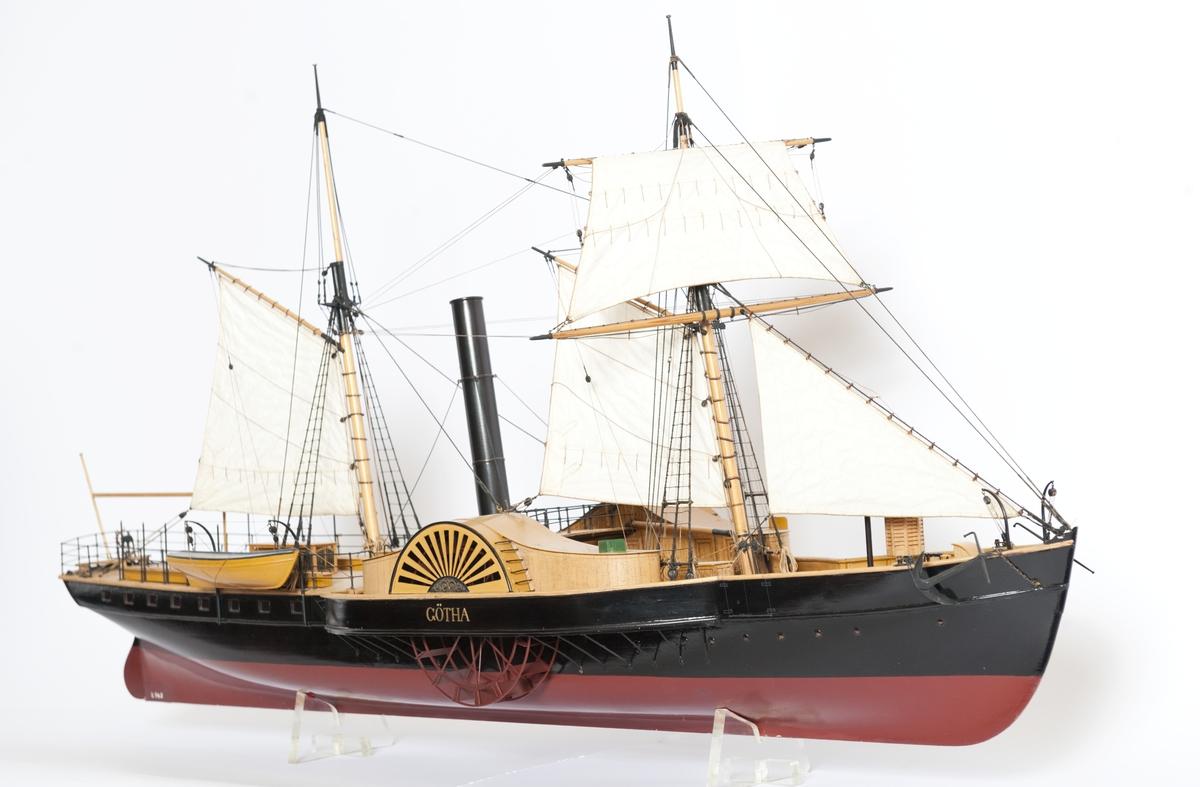 """Hjulångf. """"Götha"""", fullt utrustad modell. Hjulhus med svängda tak. Skonertriggad. Halvdäckad med två skylight, 1 livbåt. Namn i guldbokstäver på hjulhussidan. Gulmålad inombords.   Vattenlinjemodell"""