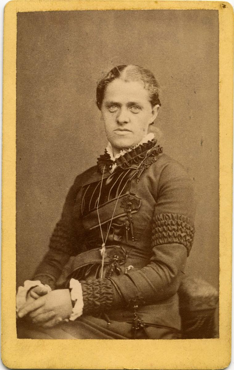 """""""Frøken Trine Bekner, Vardø"""" står det på visittkortet. Nederst på kortet står det """"K.H. eller K.R., født 1849. Til Ane Bersvendsen. Det finnes ingen opplysninger om Trine Bekner i Digitalarkivet, men Ane Bersvendsen kan være Ane Elisabeth Sørensdatter Bersvendsen, født 12.april 1863 i Nord-Lenangen, Lyngen, Troms. Men det kan også være Ane Lovise Bersvendsdatter, født 18.08.1909 på Strømsneset, datter av Bersvend Bersvendsen, født 15.06.1878 på Strømsneset. Sistnevntes far var Gårdbruker og selveier med bosted Vatten, Straumsnes under folketelling i 1910."""