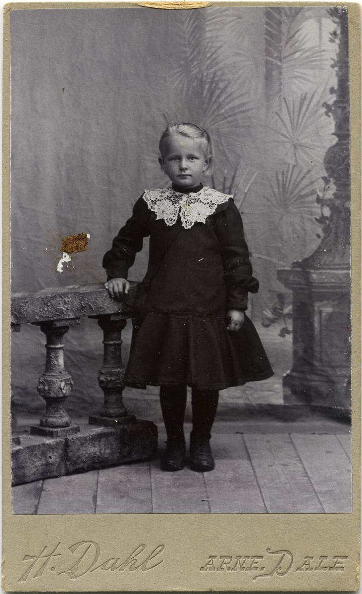 En liten jente står ved siden av et gelender.