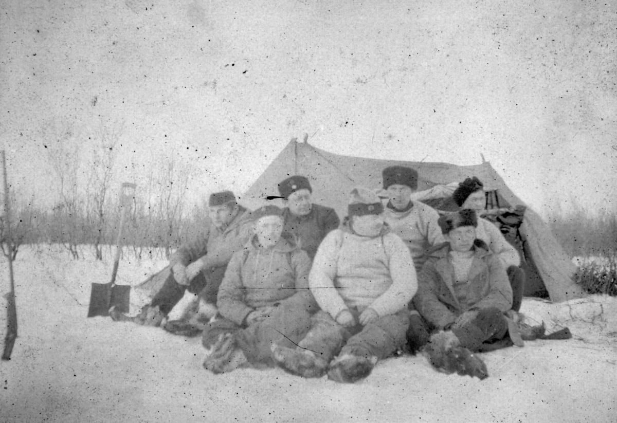 """""""Vinterøvelse Nyborgmoen. Nr.2 bak: Lebesby, nr.2 foran: Nærdrum."""" Ernst J. Lebesby og Georg Nerdrum sitter i første rekke midten. Mennene har på seg vinterklær og skaller."""