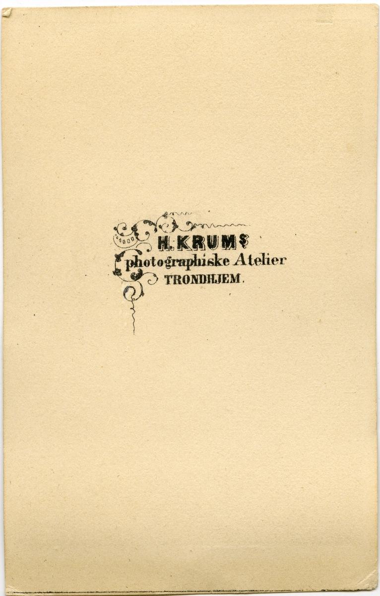 """Ukjent kvinne. Fotografert av H. Krum. Bakside av visittkort en tekst: """"H. Krum - Photographiske Atelier Trondjem""""."""