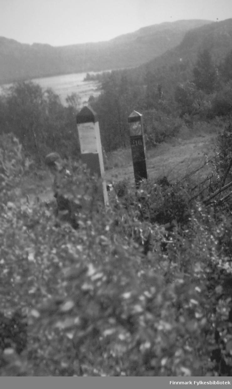 """Snikfotografering av den norsk-russiske grensa. Bildet er tatt ved Grense-Jakobselv ca. 1952-53.  Kommentar fra Kurt Røst 24.10.2010: """"Jeg tviler sterkt på at dette bilde er tatt i Grensen, men mener bestemt at det er tatt ved Skafferhullet. I Grensen finnes ikke Norsk og Russiske grensestolper på samme side av elva, da elva skiller landene, men ved Skafferhullet kommer russisk land på norsk side. Boris Gleb""""."""