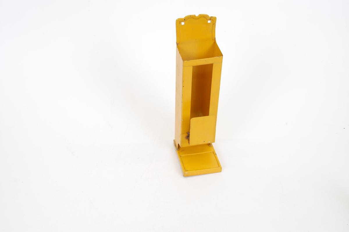 """Form: rektangulær """"sylinder"""", åpning øverst og nederst, smal åpning i front og metalldel festet nederst ved åpningen. Med fot"""