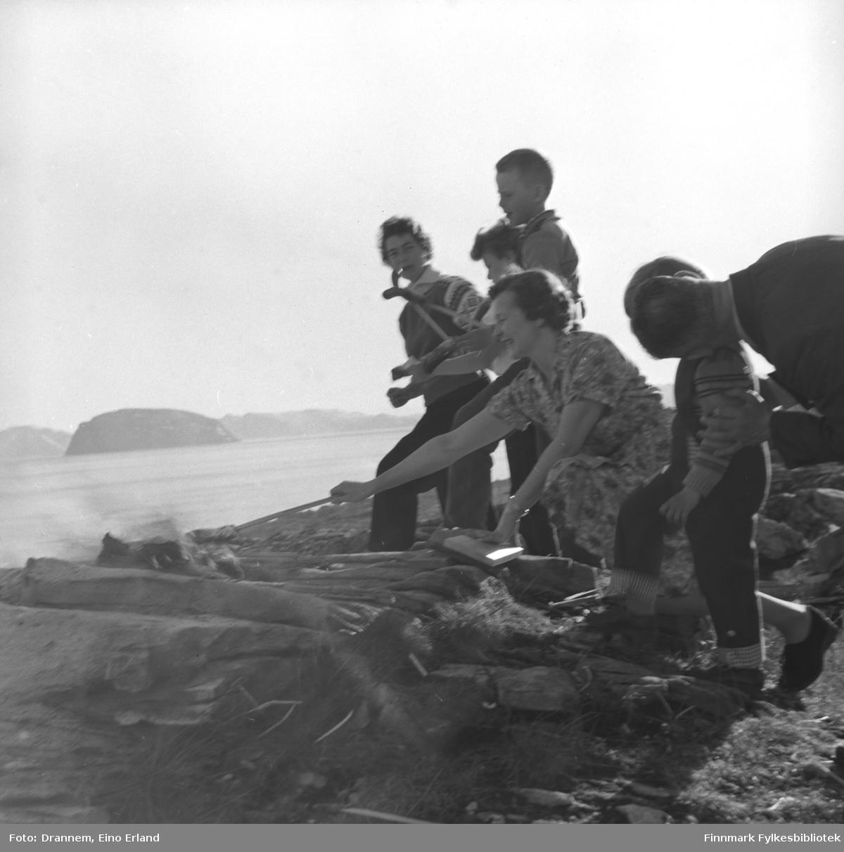 St. Hansfeiring i Hammerfest. Familiene Drannem og Sørensen steker pølser over bålet