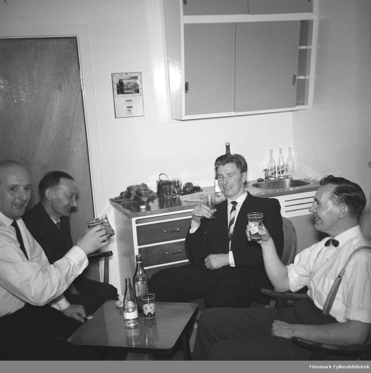 Eino Drannem fotografert i kjøkkenet sammen med sine kompiser. Alle sitter rundt et litet bord og har et glass i hånden og smiler