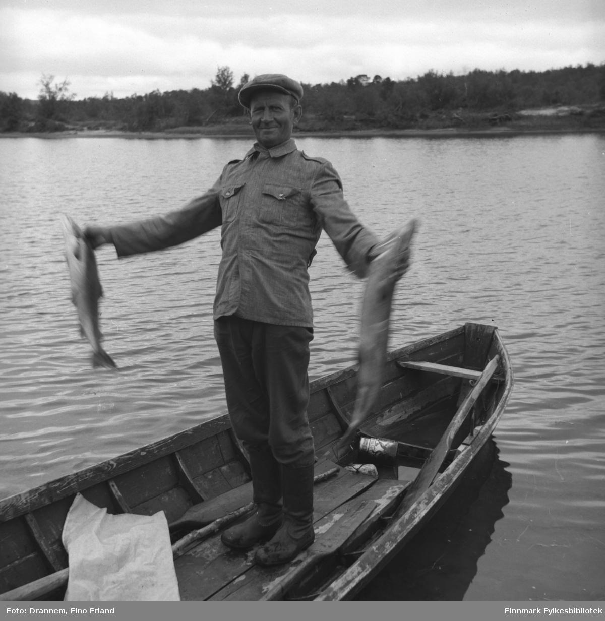 Uuno Lappalainen står i midten av en robåt og holder to store fisker i hendene.
