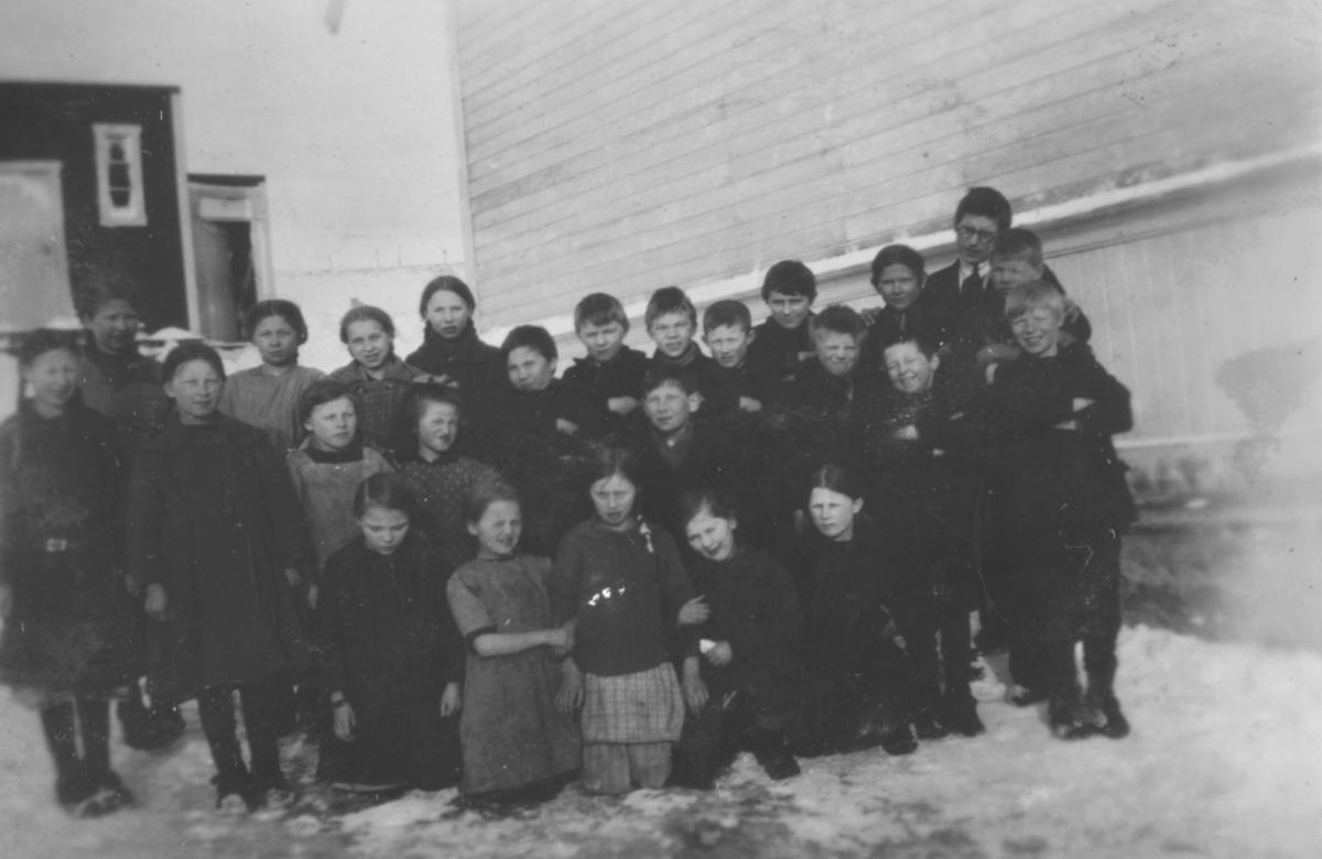 En skoleklasse og læreren fotografert utenfor en skole, sansynligvis i Kvalsund kommune.