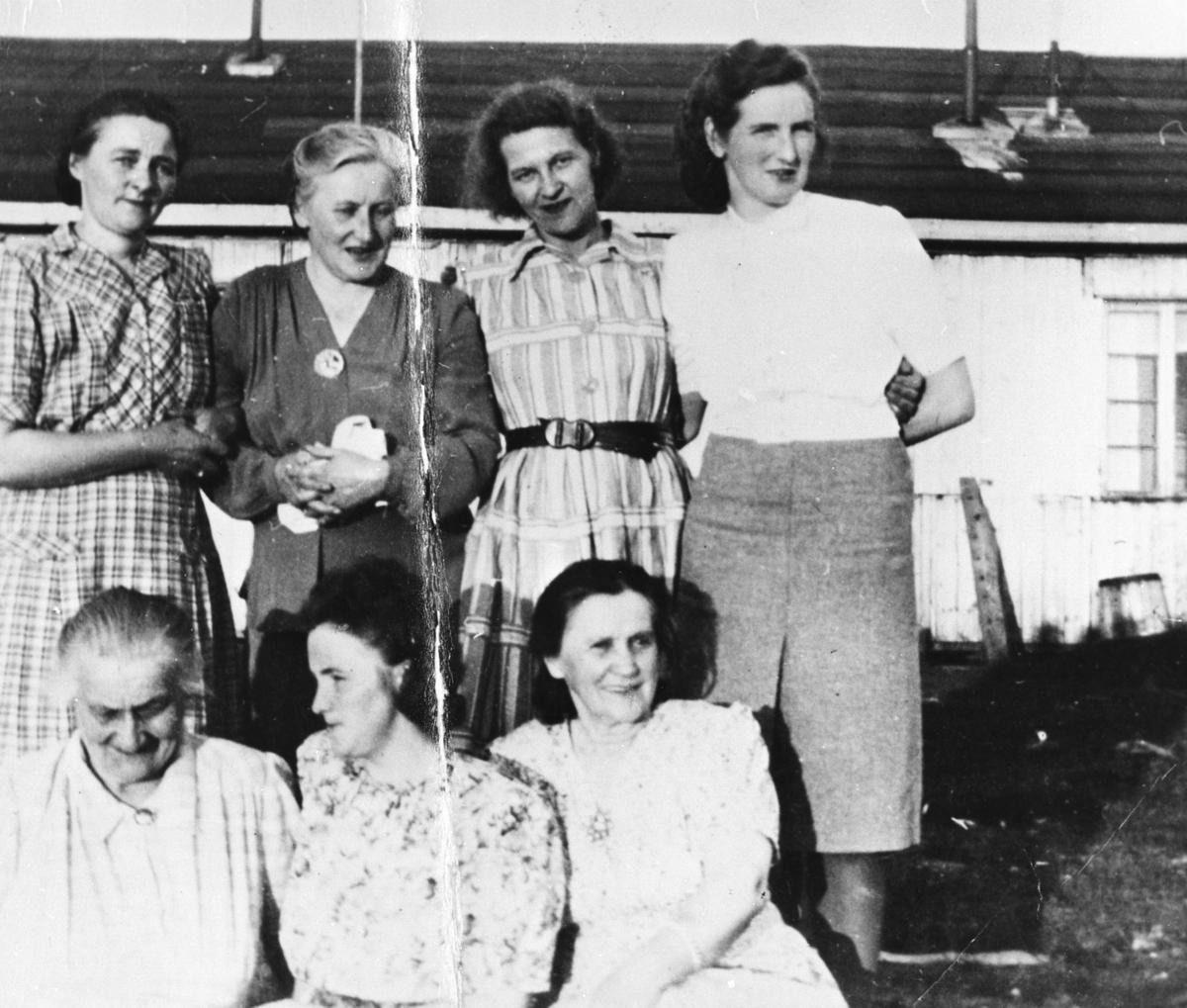 Gruppebilde av 7 damer foran en brakke. Et vindu i brakka til høure for damene. Bak fra venstre: Erna Pedersen i rutet kjole, Lalla Iversen i mørk kjole med nål i bryståpningen, Emma Kvello i stripet kjole med mørkt belte, Bjarnhild Larsen i skjørt og hvit bluse. Sittende foran: Inga Iversen i lysrutet kjole, Olaug Johnsen  og Gudrun Johnsen i blomstrete kjoler.