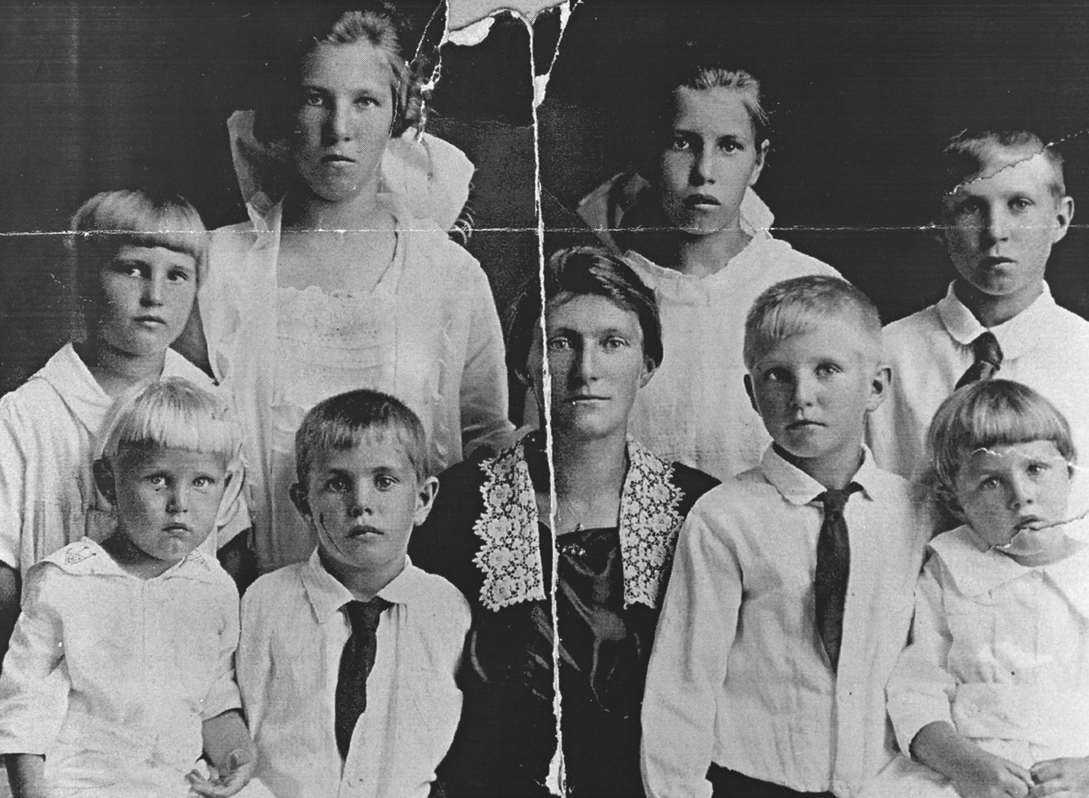Et familieportrett av Elise Lein og hennes åtte barn. Dette bildet er tatt i Amerika. Elise sitter foran i midten i sort kjole med hvit blondekrave. Barna het: Elna, Harry, Gerda, Raymond, Emma, Irene, Ernest og Oscar. Usikkert hvem som er hvem på bildet. På venstre side av Elise sitter to små gutter og til høyre én gutt og en liten pike. Stående bak to store jenter med en jente og en gutt på hver side. Alle er kledt i lyse klær, og to av guttene er kledd i slips.